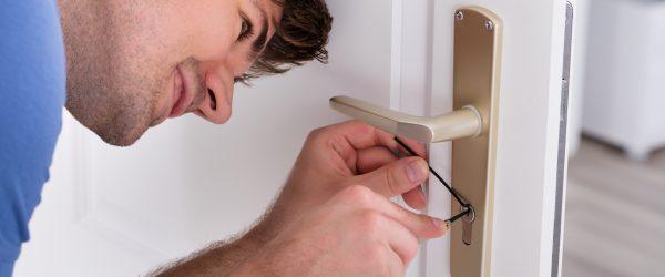 Closeup Of Young Male Lockpicker Opening Door Lock